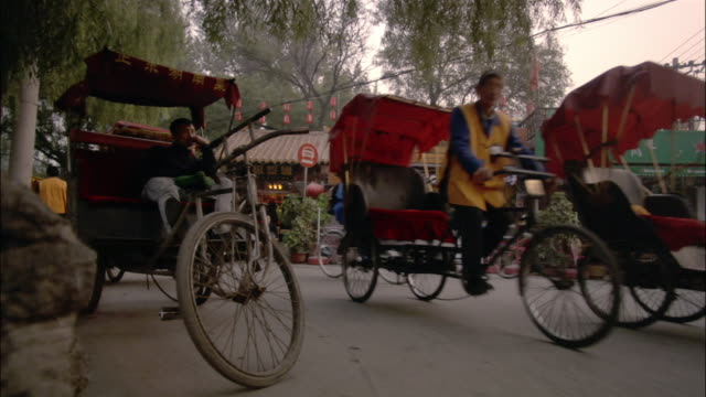 vídeos de stock, filmes e b-roll de wide shot pan pedestrians and pedicabs on road/ beijing - jinriquixá puxado por bicicleta