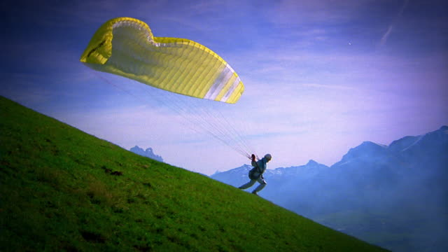 wide shot pan person in parachute lifting off from hillside with mountains in background / tyrol, austria - paragliding stock videos & royalty-free footage
