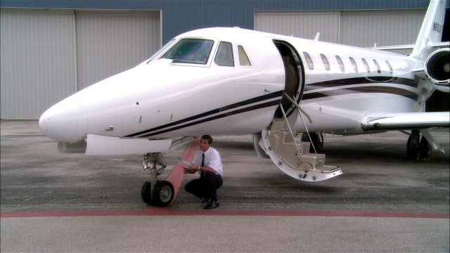 Wide shot pan Pilot inspecting private jet outside hangar at Opa Locka Airport/ Miami, Florida, USA