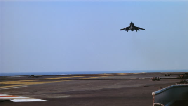 Wide shot pan plane landing on runway of aircraft carrier and taking off again