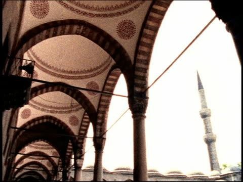 vídeos de stock, filmes e b-roll de wide shot pan porticos and minarets in courtyard of mosque / istanbul, turkey - superexposto
