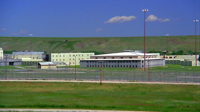 vídeos y material grabado en eventos de stock de wide shot pan prison complex - cárcel