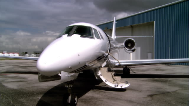 wide shot pan private jet parking outside hangar at opa locka airport/ miami, florida, usa - 飛行機格納庫点の映像素材/bロール