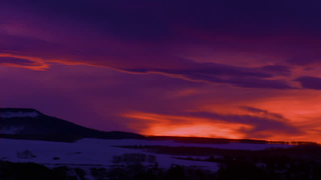 wide shot pan purple and orange sky over rocky mountains + snowy countryside at dusk / colorado - 1989 stock videos & royalty-free footage
