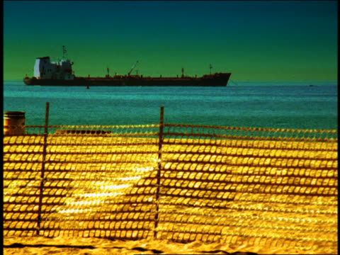 wide shot pan rack focus large oil tanker anchored in ocean with beach in foreground (flash frames) / venice beach, california - nordpazifik stock-videos und b-roll-filmmaterial