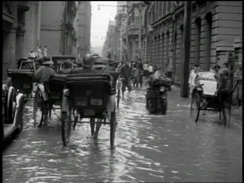 vidéos et rushes de 1932 wide shot pan rickshaws and motorcycle moving through flooded street / shanghai - pousse pousse