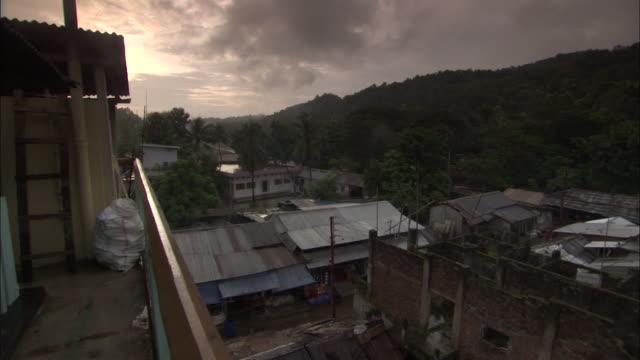 wide shot pan right - pan along rooftops of small village / bangladesh  - village stock videos & royalty-free footage