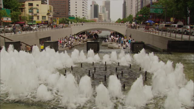wide shot pan right - people stroll around and on bridge over big fountain in cheonggye plaza in downtown seoul / seoul south korea - south korea stock videos & royalty-free footage