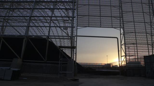 wide shot pan right to left a pile of coal sits at the sahiwal coal power plant owned by china's state owned huaneng shandong rui group at sunset in... - punjab pakistan stock videos and b-roll footage