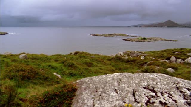 wide shot pan rocks and grassy bluffs along coastline of croagh patrick, ireland - 2002 stock videos & royalty-free footage