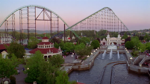 wide shot pan roller coasters and other rides at kennywood amusement park w. fountain in foreground / pennsylvania - wide stock videos and b-roll footage