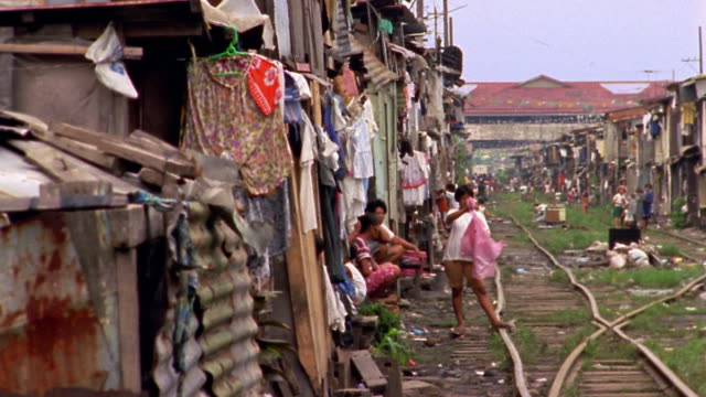 wide shot pan rows of 2-story shacks on either side of train tracks / philippines - philippines stock videos & royalty-free footage