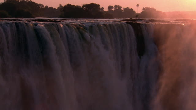 wide shot pan rushing water and mist at victoria falls / zimbabwe - victoria falls stock videos and b-roll footage
