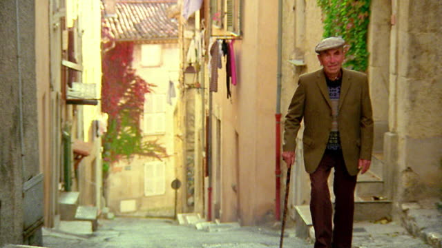 Wide shot pan senior man with cane walking up steep village road toward camera / Biot, France