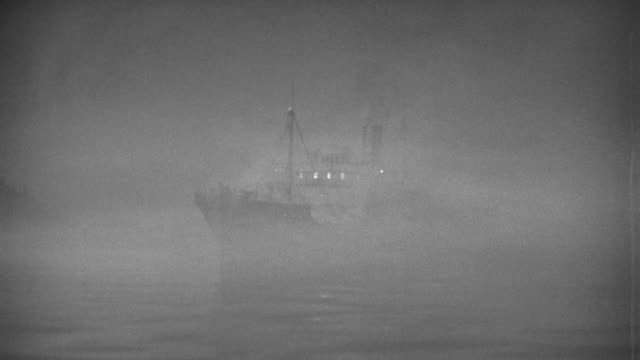 vídeos y material grabado en eventos de stock de wide shot pan ship moving on calm water in fog - aparición conceptos