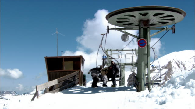 wide shot pan snowboarders snowboarding off ski lift / woman losing her balance / morzine, france - mitten stock videos and b-roll footage