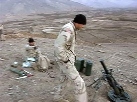 stockvideo's en b-roll-footage met wide shot pan soldier walking to check viewfinder on mortar/ afghanistan - bukken