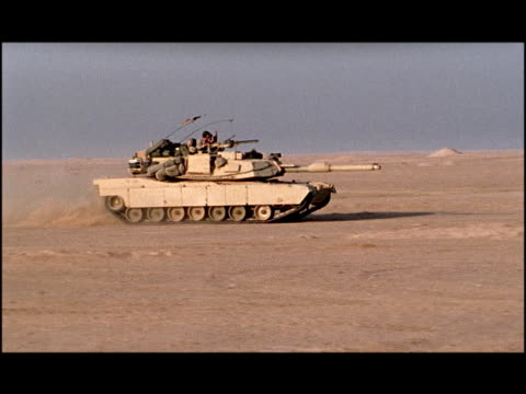 wide shot pan soldiers in m1 abrams tank driving forward, causing dust cloud behind it/ kuwait - armoured vehicle stock videos & royalty-free footage