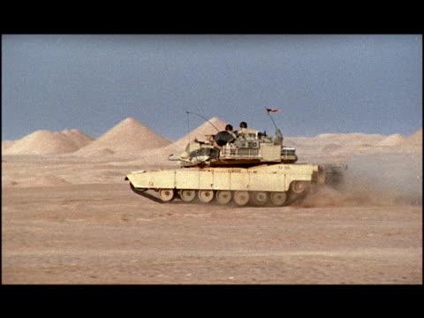 vídeos de stock, filmes e b-roll de wide shot pan soldiers in m1 abrams tank driving forward, causing dust cloud behind it/ kuwait - tanque