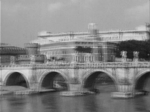 1939 wide shot pan statues of bernini's angels atop ponte sant angelo crossing tiber river near hadrian's tomb / rome, italy  - イタリア ローマ点の映像素材/bロール