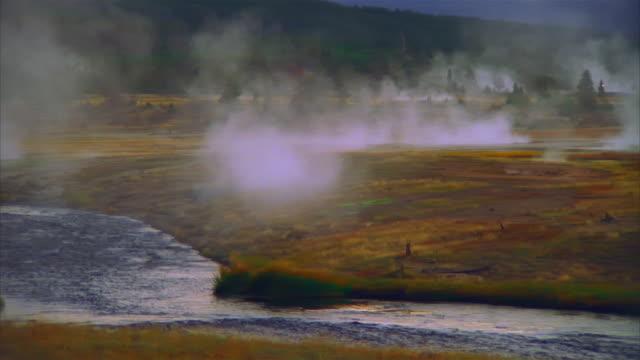 wide shot pan steam rising from hot springs / mammoth hot springs, yellowstone national park, wyoming - 景勝地点の映像素材/bロール