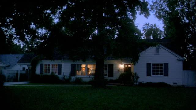 wide shot pan suburban house and yard at night - suburban stock videos & royalty-free footage