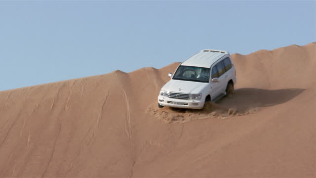 wide shot pan suv driving down sand dune/ dubai - sand dune stock videos and b-roll footage