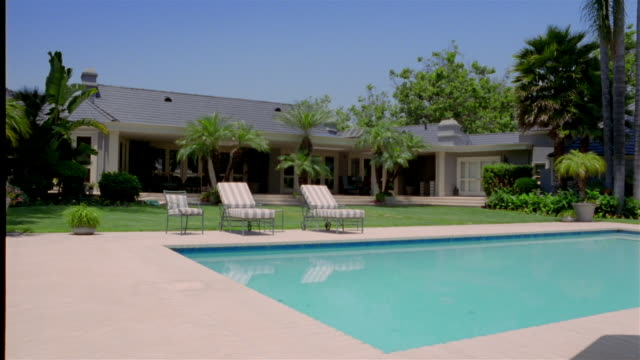 wide shot pan swimming pool and backyard area of house - patio stock videos & royalty-free footage
