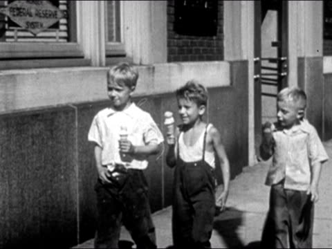 1947 wide shot pan three boys walking down city sidewalk eating ice cream cones and waving at police officer/ dearborn, michigan - ice cream cone stock videos & royalty-free footage