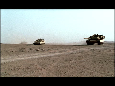 wide shot pan three tanks driving across desert, creating dust cloud/ kuwait - kuwait stock videos and b-roll footage