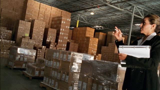 vídeos de stock e filmes b-roll de wide shot pan tilt down female clerk taking inventory in warehouse - one mature woman only