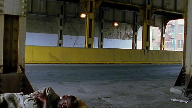vidéos et rushes de wide shot pan tilt down homeless black man sleeping beside street under overpass - mal logés