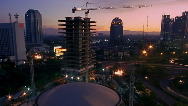 wide shot pan time lapse buildings under construction / traffic / jakarta - baugerät stock-videos und b-roll-filmmaterial