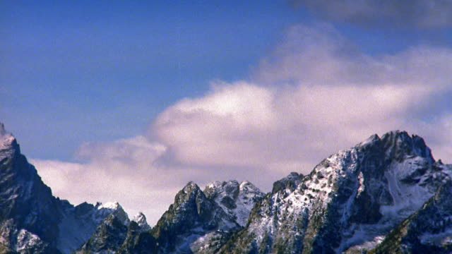 wide shot pan time lapse clouds forming in foreground over snow-capped rocky mountain peaks / grand tetons, wyoming - teton range stock videos & royalty-free footage