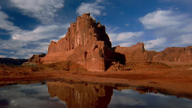 wide shot pan time lapse clouds moving behind rock formation / large puddle in foreground / arches national park - arches national park stock videos & royalty-free footage