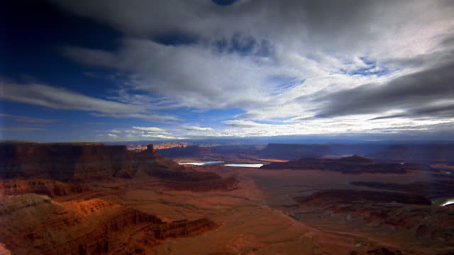 wide shot pan time lapse clouds moving over canyon / canyonlands national park - キャニオンランズ国立公園点の映像素材/bロール