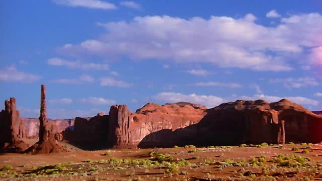 wide shot pan time lapse clouds moving over mountains and desert valley - panorering bildbanksvideor och videomaterial från bakom kulisserna