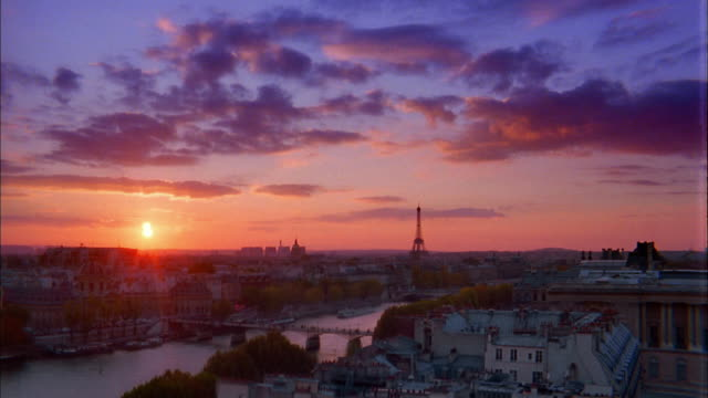 vidéos et rushes de wide shot pan time lapse clouds over river seine w/eiffel tower on horizon at sunset / paris, france - paris france