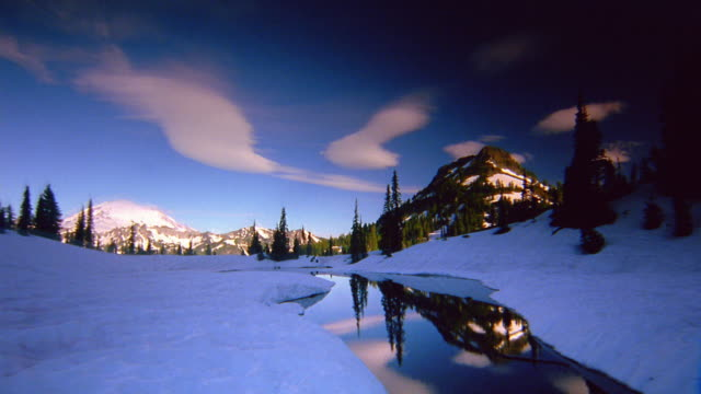 wide shot pan time lapse clouds rolling over mountains and stream with mount rainier in background / washington - mt rainier stock videos & royalty-free footage
