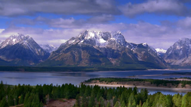 vídeos de stock, filmes e b-roll de wide shot pan time lapse shadows from clouds passing over rocky mountains with trees and lake in foreground / grand tetons - sparklondon