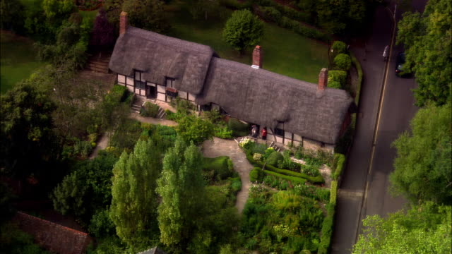 wide shot pan tourists sightseeing at anne hatherway's cottage/ shottery, warwickshire, england - thatched roof stock videos & royalty-free footage