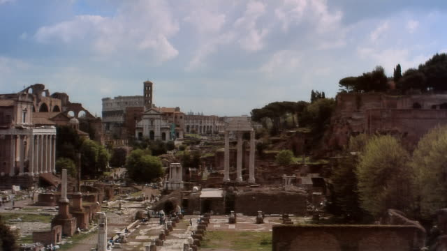 Wide shot pan Tourists walking through Roman Forum near Temple of Castor and Pollux and Temple of Vesta/ Rome, Italy