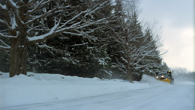 wide shot pan tow truck plowing snow-covered road / vermont - snowplough stock videos & royalty-free footage