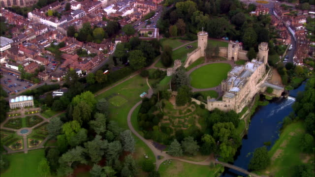 vidéos et rushes de wide shot pan town and houses surrounding warwick castle on bank of avon river/ warwick, warwickshire, england - xième siècle