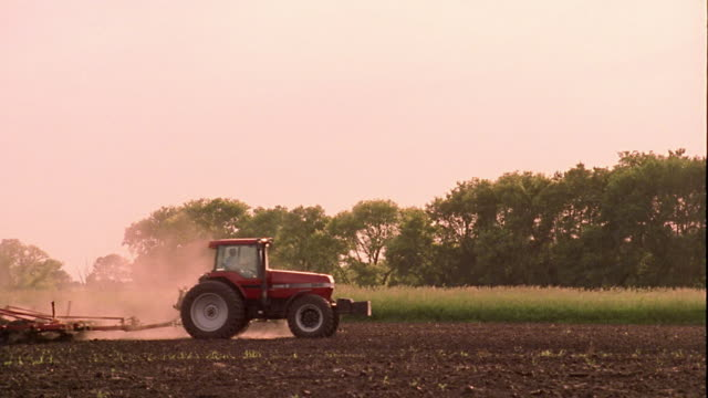 Wide shot pan tractor dragging plow across field with dust rising / Iowa