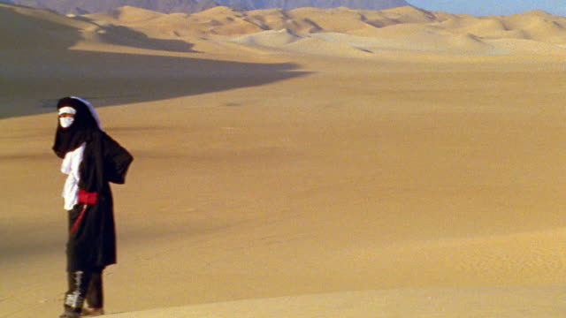 Wide shot pan Tuareg tribesman in shesh headdress and robe standing on sand dune in Sahara Desert / Niger