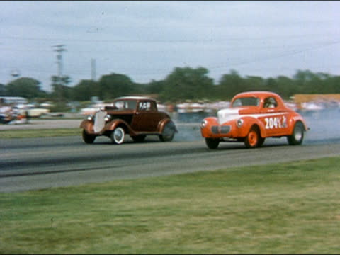 vídeos de stock e filmes b-roll de 1959 wide shot pan two cars taking off and racing along race track - 1950 1959