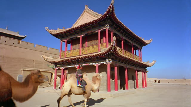 wide shot pan two men in ancient warrior uniforms riding camels past pagoda at fort jiayuguan / china - historische nachstellung stock-videos und b-roll-filmmaterial