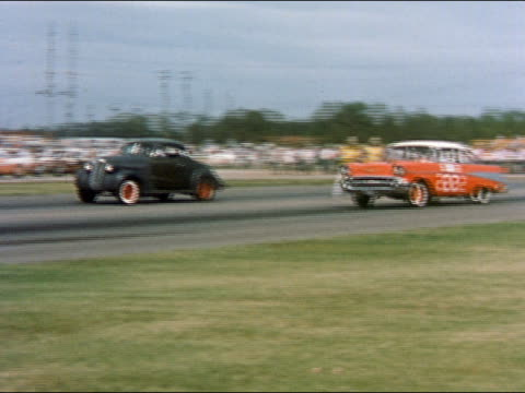 stockvideo's en b-roll-footage met 1959 wide shot pan two race cars racing on race track - prelinger archief
