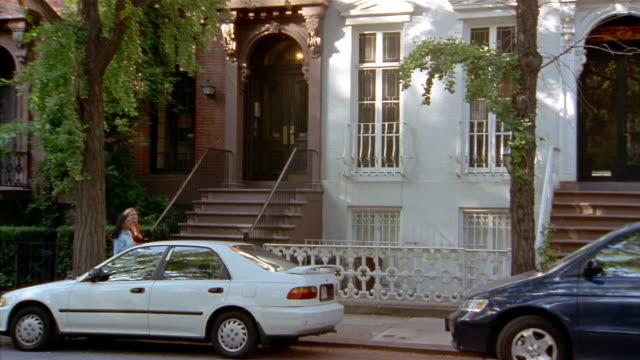 wide shot pan two women jogging past brownstones / new york city - れんが造りの家点の映像素材/bロール
